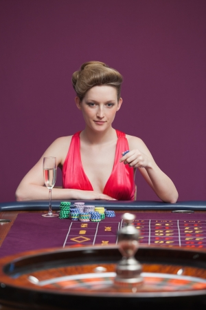Woman playing roulette with champagne in casino photo
