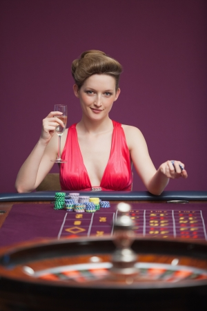 Woman playing roulette and sitting at the roulette table and drinking champagne photo