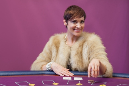 Woman sitting in a casino at table while stacking chips and placing cards Stock Photo - 16066426