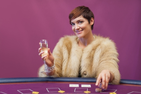 Woman with champagne at poker table in casino Stock Photo - 16066689