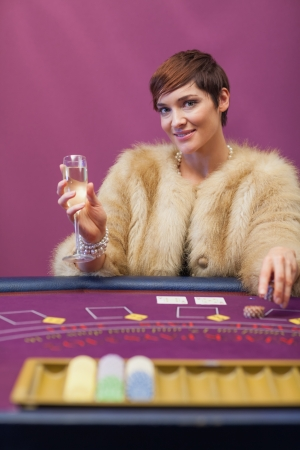 Woman sitting in a casino at table while drinking champagne and stacking chips Stock Photo - 16068561