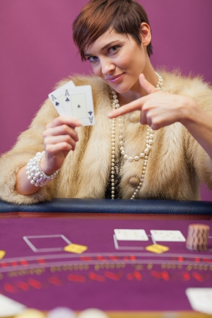 Woman in a casino sitting at table and showing cards photo