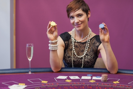 Woman at poker game holding up chips in casino photo