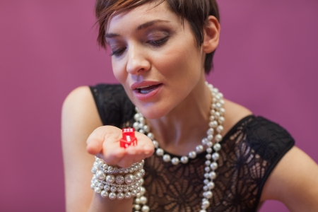 Woman blowing on dice for luck in casino Stock Photo - 16068732