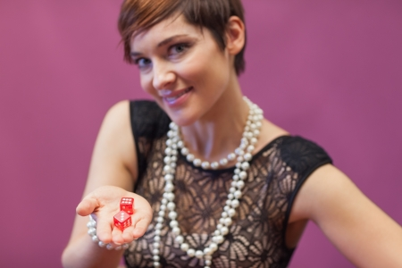 Woman in a casino holding red dices while smiling Stock Photo - 16068000