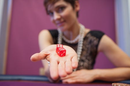 Woman sitting at table in a casino holding dices and smiling Stock Photo - 16065907