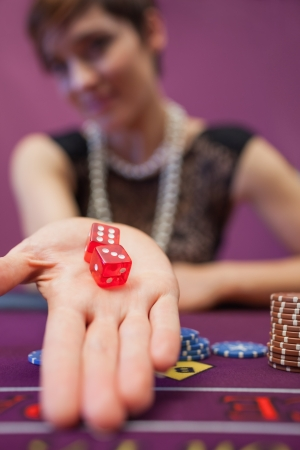 Woman sitting in a casino at table holding dices while smiling Stock Photo - 16065512