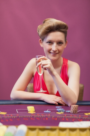 Woman sitting at table of a casino holding a glass of champagne Stock Photo - 16065782