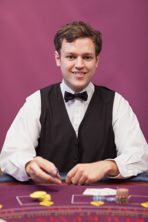 distributing: Dealer sitting at table in a casino while distributing chips