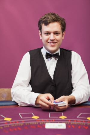 Dealer sitting at table in a casino while holding cards and smiling photo