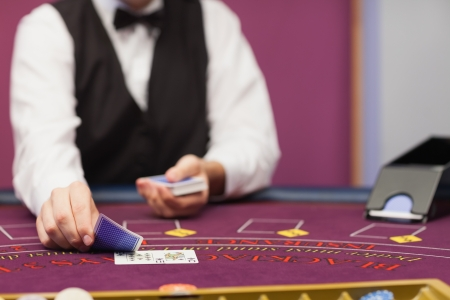 distributing: Dealer sitting in a casino at table while holding and distributing cards