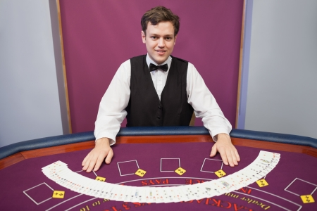 Smiling dealer with fanned out deck of cards in casino  photo