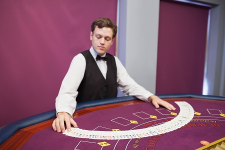 casino dealer: Dealer spreading deck of cards in casino at poker table