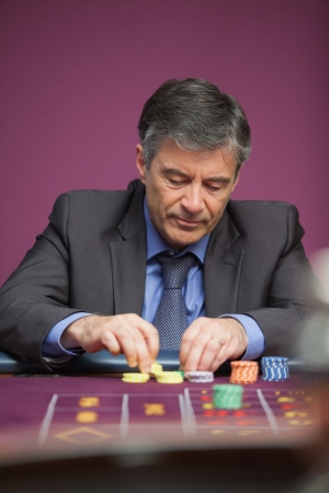 Man grabbing chips while playing roulette and sitting at table in a casino