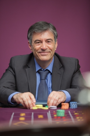 Smiling man sitting at table in a casino while playing roulette and grabbing chips photo