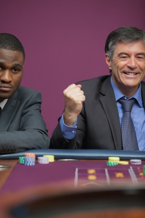 Smiling man sitting at table in a casino and celebrating roulette win photo