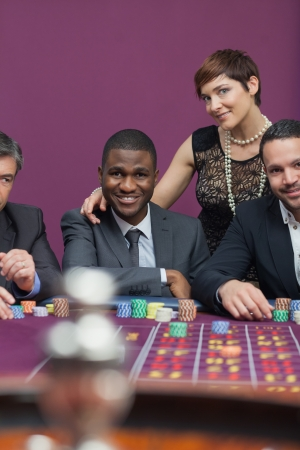 Three men and a woman at roulette table in casino photo