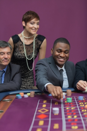 Bets being placed at roulette table in casino photo