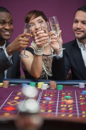 Three people toasting at roulette table in casino photo
