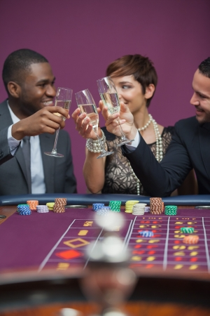 Three people playing roulette and toasting while sitting at table in a casino photo