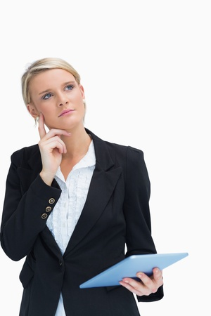 Businesswoman looking thoughtful while holding a tablet photo