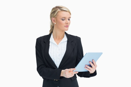 Blonde businesswoman looking at her tablet  Stock Photo - 16050159