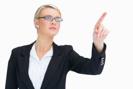 Businesswoman pointing in the air while looking thoughtful photo
