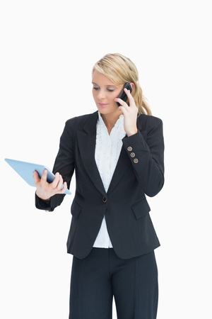 Blonde businesswoman looking at her tablet while calling Stock Photo - 16051435