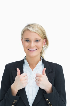 Businesswoman showing thumbs up while smiling photo