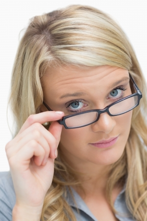 sternly: Blonde looking above her glasses sternly Stock Photo