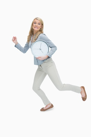 hurried: Hurried woman running while holding a big clock