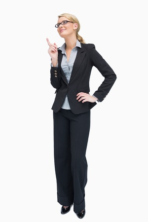 Smiling businesswoman standing and thinking while pointing up Stock Photo - 16050038