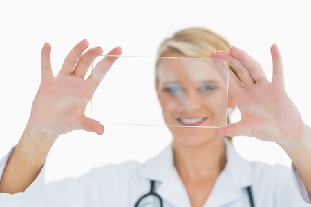 Smiling doctor in labcoat holding up clear pane Stock Photo - 16051313