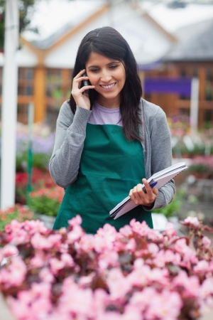 stocktaking: Black-haired woman calling while doing stocktaking in garden centre