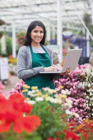 Brunette typing on the laptop in the garden centre while smiling photo