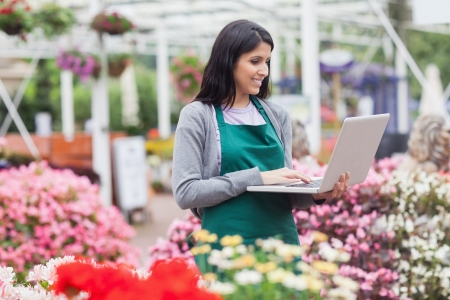 garden center: Woman doing stocktaking with laptop in garden centre