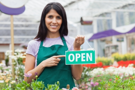 Woman in garden center pointing at the open-sign while smiling photo