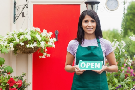 Florist holding open-sign while smiling in garden center photo