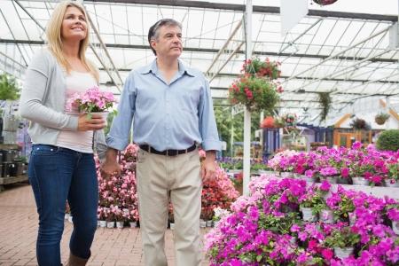 Couple walking around garden center with woman holding pink flower