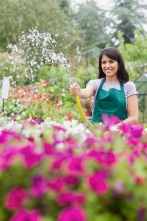 Woman having fun while watering plants in garden center with hose photo
