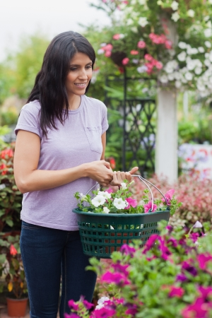 Woman putting flowers into basket while smiling photo