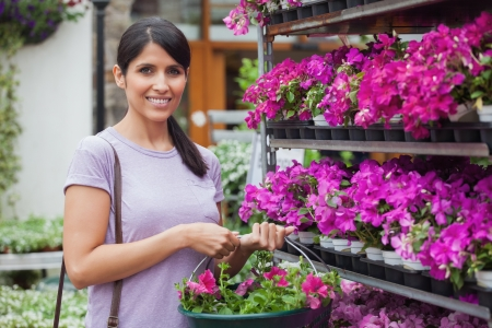 Woman holding basket and buying pink flowers photo