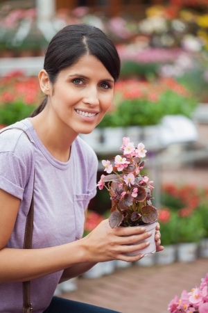 Woman holding a flower while smiling outside the garden centre photo