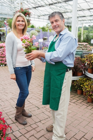 Woman buying flowers in garden centre photo
