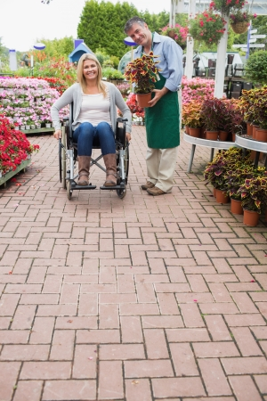 Garden center employee holding a plant and woman in wheelchair  photo