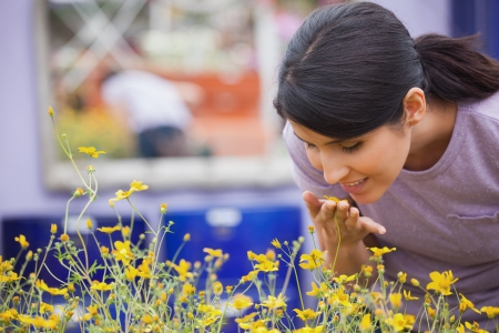 Woman smelling yellow flowers happily in garden center photo
