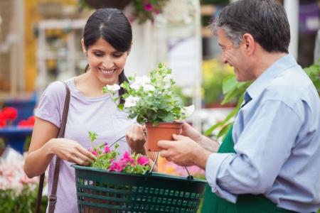 Woman buying plants in garden center