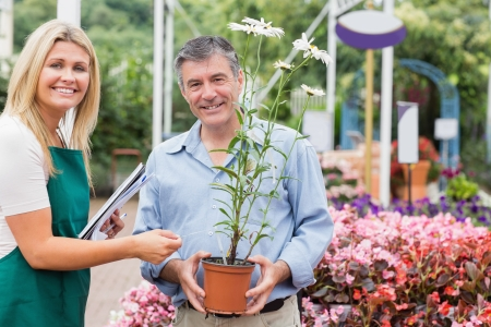 Gardener giving advice to customer while holding a flower and smiling Stock Photo - 16078701