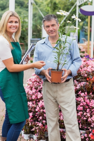 Florist giving advice to customer while smiling in garden center Stock Photo - 16078799