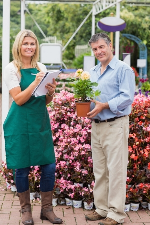 noting: Employee taking notes and customer holding plant standing in garden center